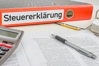 An orange folder with the label Tax return - Steuererklaerung (German)