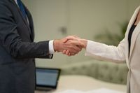 Female and male handshake. Young freelancers working together doing handshake at business meeting at the office. Two young business people standing in the office, shaking hands