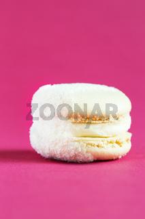 white Cake macaron or macaroon on pink background.
