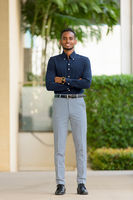 Full length shot of handsome African businessman outdoors at rooftop garden with arms crossed
