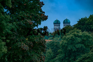 Munich famous twin towers of the Frauenkirche protude over so autumn colored trees from the viewpoint of the Englisch Garden in Munich.