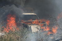 Burning car in a field covered by fire