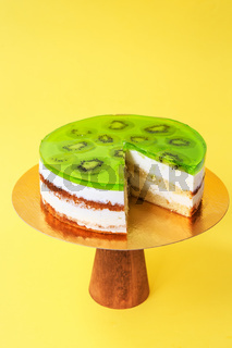 Sliced Birthday cake on the wooden cake stand. Beautiful sponge cake on the paper background. Copy space. Food photography for recipe.
