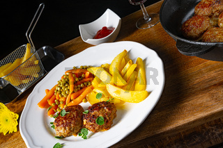 Homemade meatballs with french fries and vegetables