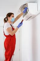 Female technician using smartphone and repairing air conditioner