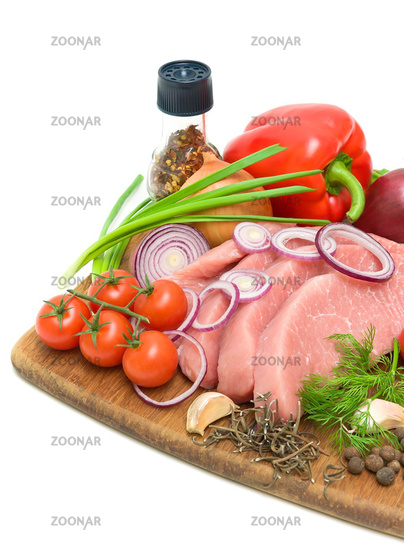 vegetables and raw meat on a cutting board on a white background