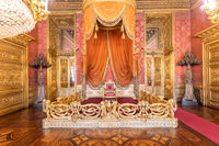 Old throne room interior with chair in luxury palace. Red and gold antique Baroque style.
