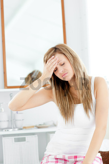 Dejected woman having a headache sitting in the bathroom