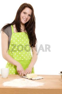 glückliche frau schneidet butter zum backen