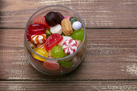 Candies in a jar on a wooden background. Multi-colored caramel. Sweets.