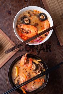 miso soup with mussels, shrimps , shiitake mushrooms and vegatables. served at dark brown wooden table. flat layen table. flat lay
