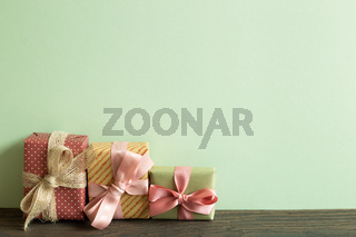 Colorful gift boxes on wooden table. green wall background