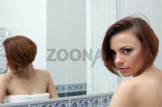 Beautiful woman near mirror in bathroom