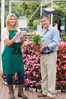 Employee and customer standing in garden center