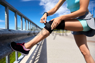 young woman in knee band doing sports outdoors