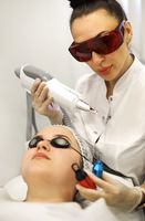 Woman treating client face with laser