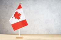 Canada table flag on white textured wall. Copy space for text, designs or drawings