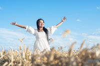 Portrait of happy young woman in a white dress, on a wheat field. Lifestyle and happiness concept. Woman with open arms .