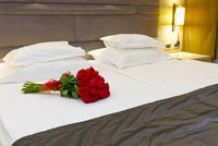 bouquet of red roses on the bed in a hotel room for honeymoon. romantic meeting of guests at the hotel.
