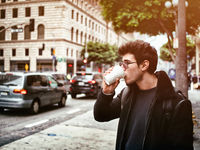 Attractive young man in modern city center drinking coffee