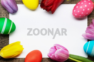 Easter egg and tulips on wood