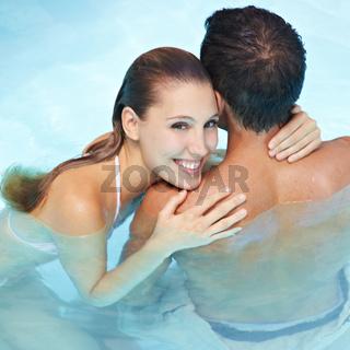 Frau umarmt Mann im Wasser