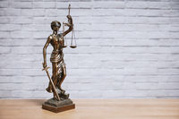 Lady Justice or Justitia the goddess of justice statue on desk - legal law legislation concept