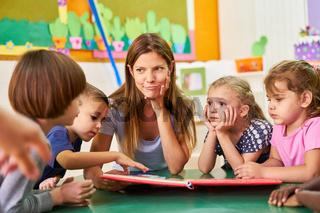 Kindergärtnerin und Kinder lesen und spielen zusammen
