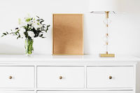 Golden vertical frame and bouquet of fresh flowers on white furniture, luxury home decor and design for mockup creation
