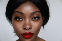 Black African and beautiful woman with make-up posing over white background.