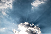 Freedom and spirituality concept. Sunbeams and clouds on a blue sky