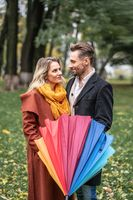 Looking in to the eyes of each other with closed rainbow umbrella beautiful in love couple standing in the park under a. A beautiful couple the autumn park in rainy weather