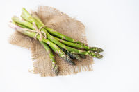 Fresh green asparagus tied with thread and lying on sacking. Healthy and wholesome food concept. View from above.
