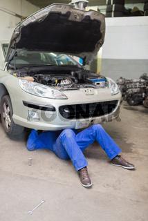 Man repairing car in garage