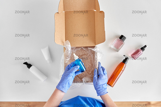 hands in gloves packing parcel box with cosmetics