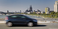 Car in motion on the Zoo bridge with the cathedral in the background, Cologne, Germany, Europe