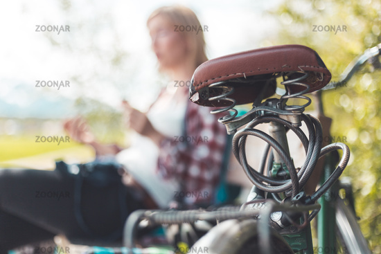 Retro bike tour: Seat of bike outdoors, rural scene, blonde girl sitting in blurry background