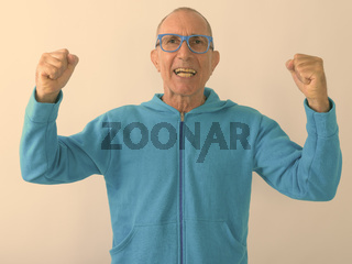 Studio shot of happy bald senior man smiling and looking excited while wearing eyeglasses against white background