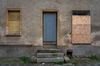 Boarded up windows and a door in an old building.