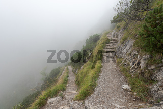 Steep hiking path in the alps on cold autumn day with mist and fog