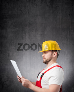 A surprised construction worker holding papers or documents