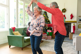 Happy caucasian senior couple dancing in living room at christmas time