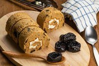 Hogh angle view of homemade sponge cake roll and dried pitted prune fruit on wooden board.