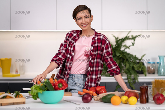 Happy of new home pretty housewife cutting ingredients on table cooking lunch standing in the kitchen with one hand on a side. Healthy lifestyle. Cooking at home for loving family. New house concept