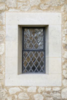 Central leaded Church window surrounded by stonework.