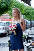 a beautiful young girl in summer dress with a bunch of flowers in pavement cafe