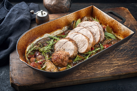 Traditional braised veal roll roast sliced with vegetable and herbs offered as close-up in a rustic skillet