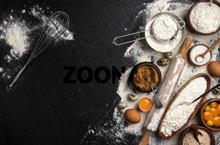 Baking ingredients on black background with copy space
