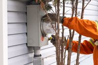 A smart electric meter on wall is being installed
