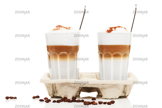two latte macchiato with chocolate powder in a cup